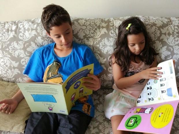 Filhos da ilustradora, Pedro e Luísa observam o livro de Julianna e Flávio (Foto: Arquivo Pessoal/Julianna Rodrigues)