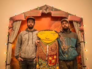 Otávio e Gustavo Pandolfo, conhecidos como Osgêmeos, em frente a uma das obras de 'A ópera da Lua', que está no galpão Fortes Vilaça, em SP (Foto: Guilherme Tosetto/G1)