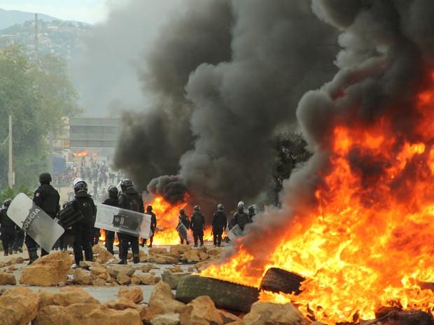Oficiais aguardam perto de barricada em chamas após confrontos com sindicato de professores perto de Nochixtlan, no México (Foto: Jorge Luis Plata/ Reuters)