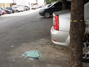 Vidro de carro que explodiu quebrado no chão (Foto: Isabella Formiga/G1)