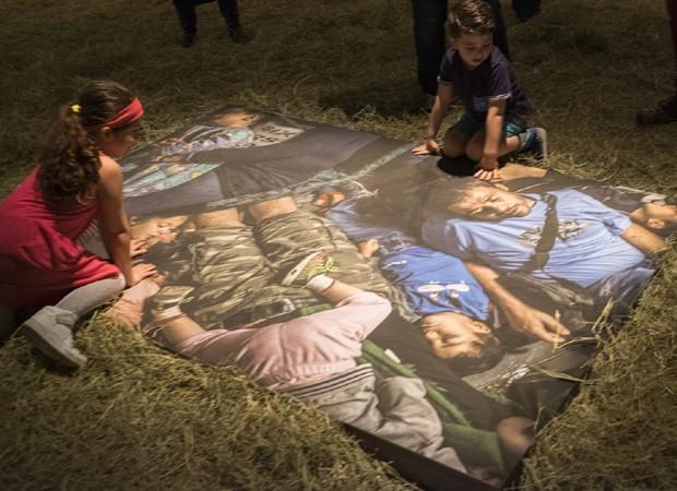 Crianças sírias veem fotos de exposição no MIS-SP (Foto: Divulgação)