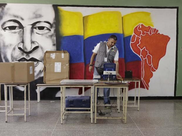 Funcionário do Conselho Eleitoral Nacional configura máquina de votação em frente a mural com a figura do ex-presidente Hugo Chávez em escola de Caracas (Foto:  REUTERS/Marco Bello )