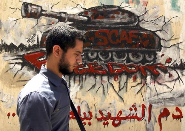 Egípcio passa em frente a tanque pintado em muro próximo à Praça Tahrir, no Cairo, em protesto contra a Junta Militar, nesta sexta-feira (18) (Foto: Reuters)