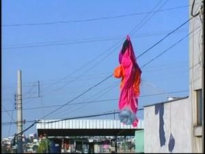 Paraquedas ficou preso no fio de energia elétrica (Foto: Reprodução/TV Integração)