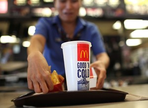 Atendente serve pedido em loja do McDonald's Fast food Junk food (Foto: Getty Images)