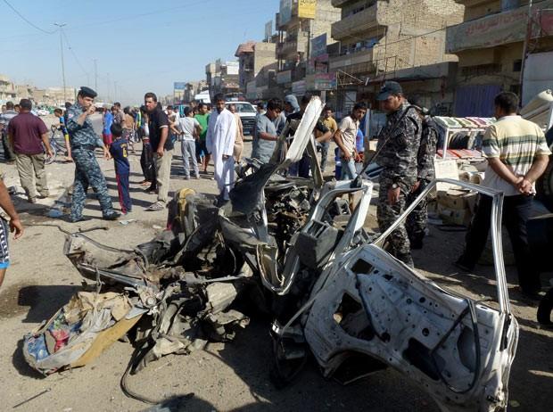 Moradores e policiais observam local de explosão de carro-bomba nesta segunda-feira (29) em Cidade Sadr, em Bagdá (Foto: AFP)