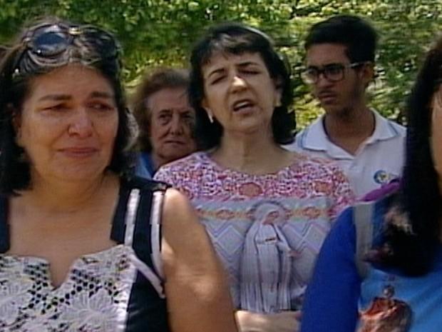 Moradores choram e cantam em local onde imagens de santos foram destruídas por vandalismo (Foto: Reprodução/TV Anhanguera)