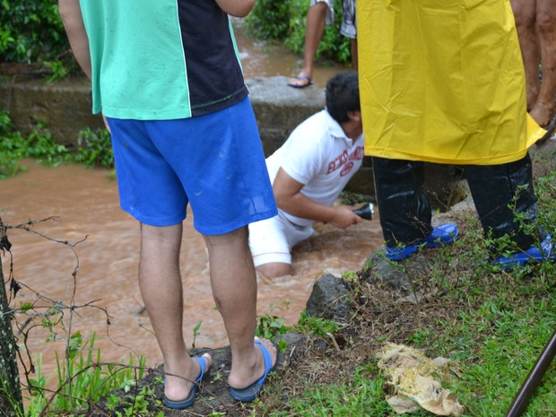 Homens tentam localizar menino em tubulação de esgoto (Foto: Eduardo Godinho/Rádio Aurora)