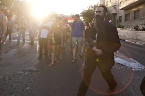 Fotógrafo flagrou o momento em que o homem sacou a faca de dentro do paletó antes de atacar participantes da parada gay (Foto: Sebastian Scheiner/AP)