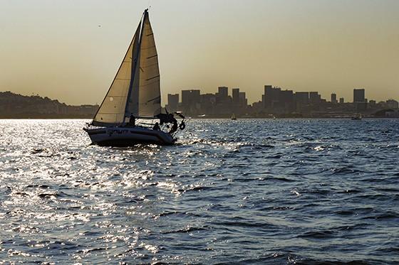 Um veleiro desliza sobre as águas da Baía de Guanabara com os espigões do Centro da cidade ao fundo (Foto: © Haroldo Castro/ÉPOCA)