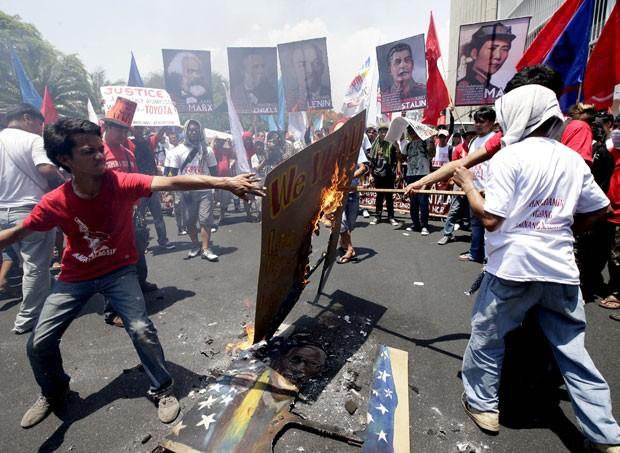 Em Manila, manifestantes queimaram cartazes com fotos do presidente dos EUA, Barack Obama,  e do presidente das Filipinas, Benigno Aquino III. (Foto: Bullit Marquez/AP)