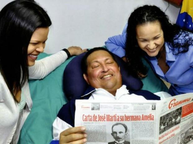 Venezuela divulga primeira imagem de Chávez após cirurgia. Acompanhado de suas filhas o presidente sorri enquanto lê o jornal. (Foto: Divulgação)