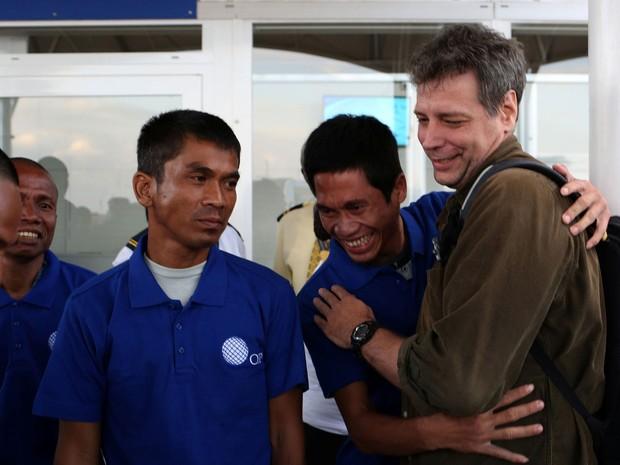 Um dos homens capturados por piratas somalis há quase cinco anos abraça Michael Scott Moore, um ex-refém que ajudou nas negociações para a libertação deles, ao chegar ao aeroporto internacional de Nairobi, no Quênia, no domingo (23) (Foto: Reuters/Siegfried Modola)