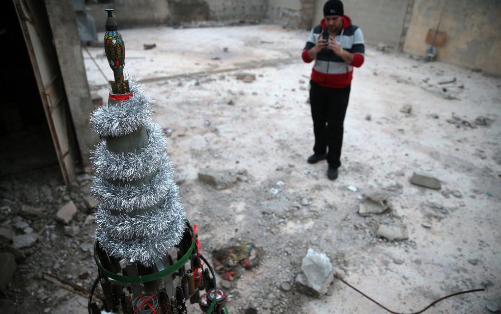 Akram Abu al-Foz tira foto de uma árvore de Natal decorada com projéteis vazios que ele recolheu e pintou na cidade em Douma, na Síria (Foto: Bassam Khabieh/Reuters)