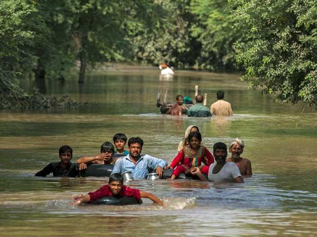 Grupos de pessoas atravessam área inundada. (Foto: Zohra Bensemra / Reuters)