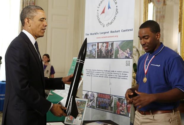 Obama segura um foguete produzido pelo estudante Darius Hooker, premiado durante a Feira de Ciências da Casa Branca, realizada nesta segunda-feira (22) em Washington, nos EUA. Vários projetos de ciências, engenharia e matemática foram apresentados por jov (Foto: Larry Downing/Reuters)