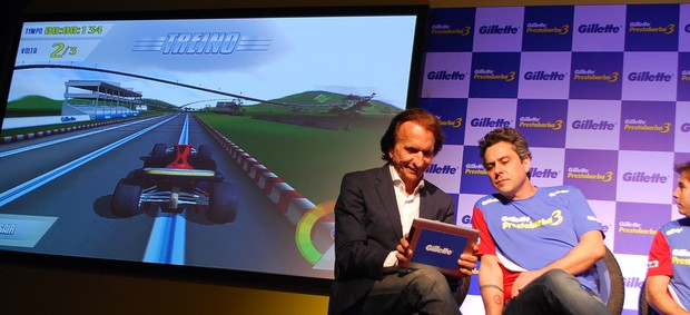 Emerson Fittipaldi recebe ajuda de Alexandre Nero no videogame (Foto: Marcos Guerra)
