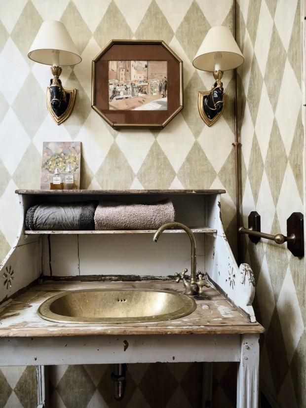 """Lavabo. As obras de arte aparecem em todos os cômodos da casa de maneira bastante informal, já que os proprietários as veem como objetos """"comuns"""" do seu dia a dia. O móvel antigo abriga a pia e ainda guarda toalhas (Foto: Fabrizio Cicconi / Living Inside)"""