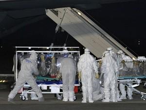 Foto cedida pela Força Aérea Italiana mostra pessoas vestidas em trajes de proteção biológica durante o  transporte de um médico que testou positivo para o vírus ebola em um aeroporto militar perto de Roma. É primeiro caso confirmado da doença na Itália (Foto: Força Aérea Italiana/AP)