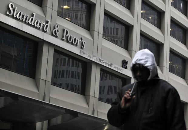 Homem caminha diante da sede da agência classificatória de risco Standard & Poor's em Nova York (Foto: Brendan McDermid/Reuters)