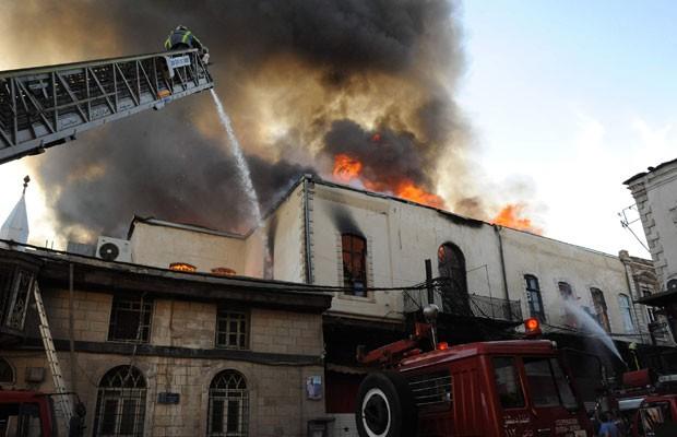 Bombeiros combatem fogo provocado por um bombardeio em Damasco, na Síria. (Foto: France Presse)