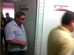 Um dos suspeitos, que estava no carro da Sima, chega à Delegacia Geral da Polícia Civil. (Foto: Fabiana De Mutiis/G1)