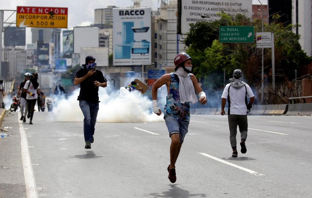 Manifestantes correm de bombas de gás lacrimogênio, neste sábado (13), em Caracas (Foto: REUTERS/Marco Bello)
