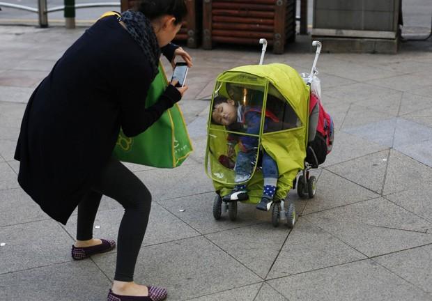 Mãe não perdeu tempo e tirou uma foto da soneca do filho enquanto passeavam pelo centro de Seul, na Coreia do Sul (Foto: Kin Cheung/AP)