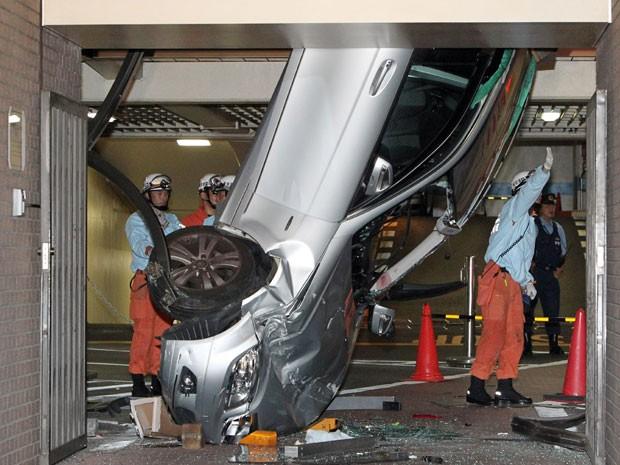 Carro ficou pendurado entre dois andares de garagem de hotel no Japão (Foto: STR/AFP)