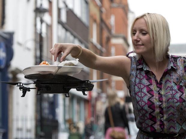 Cliente pega comida em bandeja voadora (Foto: Neil Hall/Reuters)