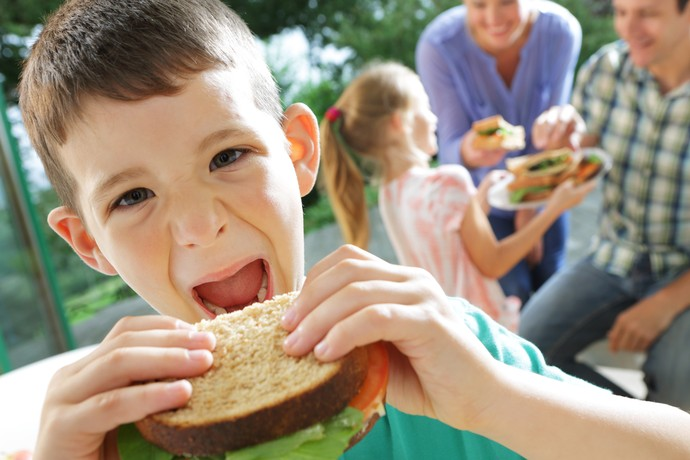 Garoto comendo sanduíche euatleta (Foto: Getty Images)