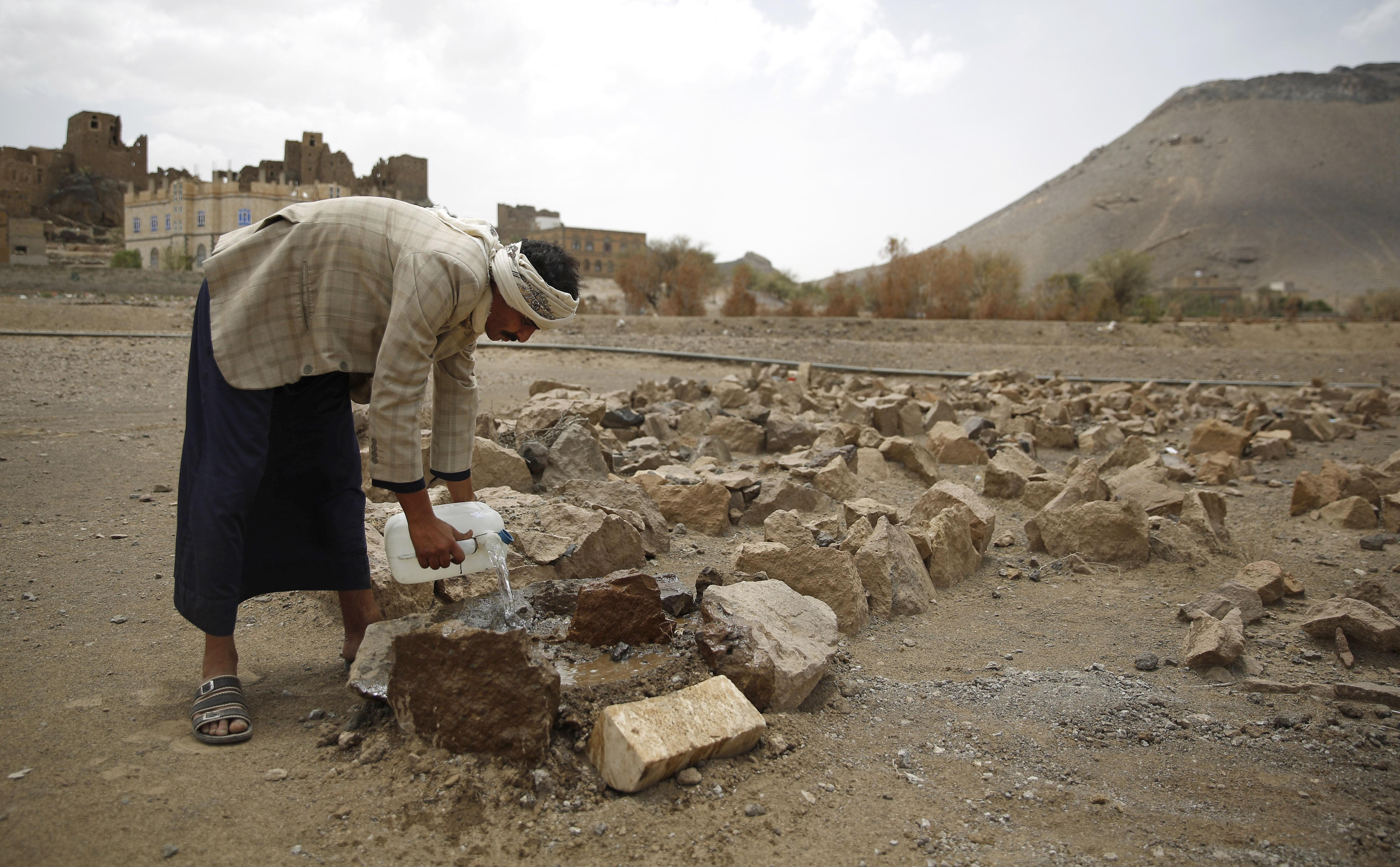 O pai de Udai rega sua sepultura, marcada apenas por pedras (Foto: AP Photo/Maad al-Zikry)