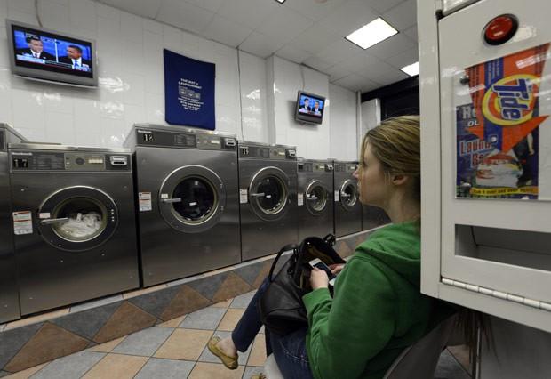 Americana assiste ao debate enquanto espera em lavanderia de Manhattan na noite desta segunda (22) (Foto: AFP)