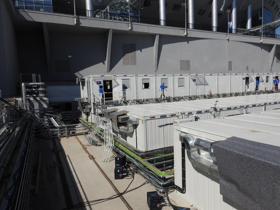 Espaço para saída do gramado, ao lado do estádio, está com estrutura de emissoras de televisão. É possível ver um dos trilhos (Foto: Thiago Dias)
