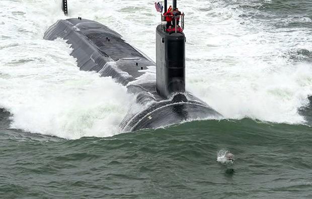 Golfinho é visto saltando à frente de um submarino nuclear americano em testes na costa da Virginia (Foto: Iberpress)