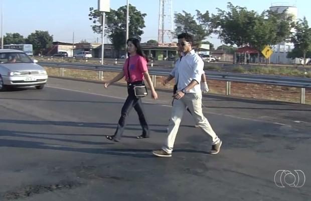 Passageiros se arriscam ao atravessar rodovia para pegar ônibus em Goiânia (Foto: Reprodução/ TV Anhanguera)