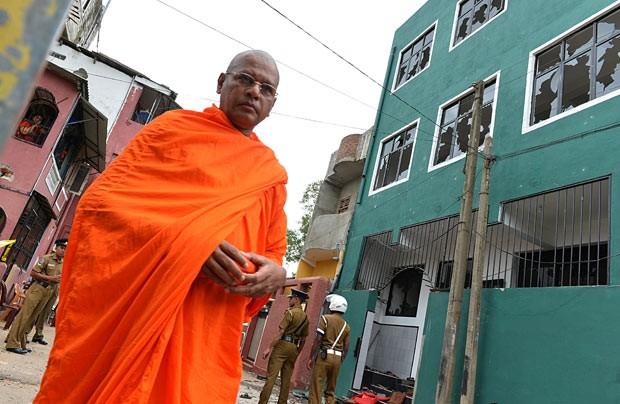 Monge budista em frente à mesquita vandalizada em Colombo, capital do Sri Lanka (Foto: Ishara S. Kodikara/AFP)