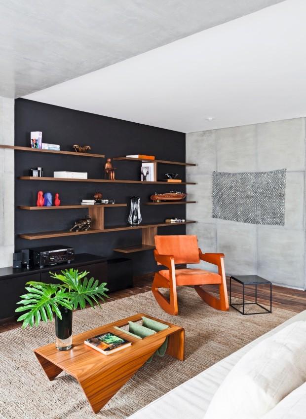 A parede pintada de preto fosco destaca as prateleiras com 3 cm de espessura e fixação por ferros. Da mesma cor é o móvel baixo laqueado da Yamato Marcenaria. Poltrona, mesa lateral e mesa de centro da Etel Interiores (Foto: Maíra Acayaba / Divulgação)
