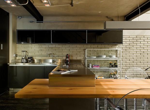 A cozinha conta com armários pretos, da Florense, tampo de aço, da Mekal, mesa de pinho maciço, da Marcenaria Inovart, cadeiras Tosca, da Micasa, e iluminação Wall Lamps (Foto: Divulgação)