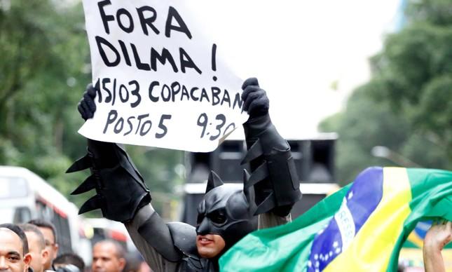 O Batman das manifestações segurando um cartaz pedindo o impeachment da presidente Dilma