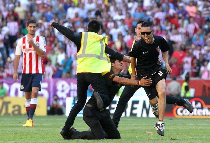 Torcedor do Atlas tenta escapar de policial após invadir o gramado (Foto: EFE)