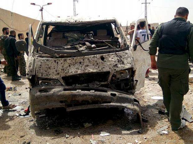 Soldados sírios inspecionam carro-bomba que explodiu em Sayeda Zeinab, distrito ao sul de Damasco, nesta segunda-feira (25) (Foto: Sana via Reuters )