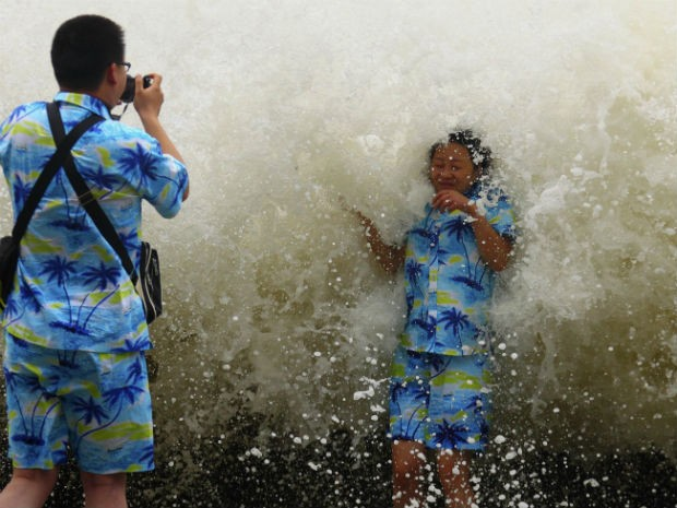 Turista tira foto com onda na China. Ondas chegaram a nove metros de altura após passagem de tufão pelo país. (Foto: Reuters/Stringer )