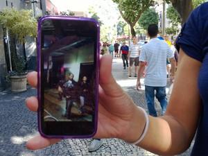 Moradora que não quis se identificar mostra fotos de seu celular de jovens saqueando a loja (Foto: Lilian Quaino/G1)