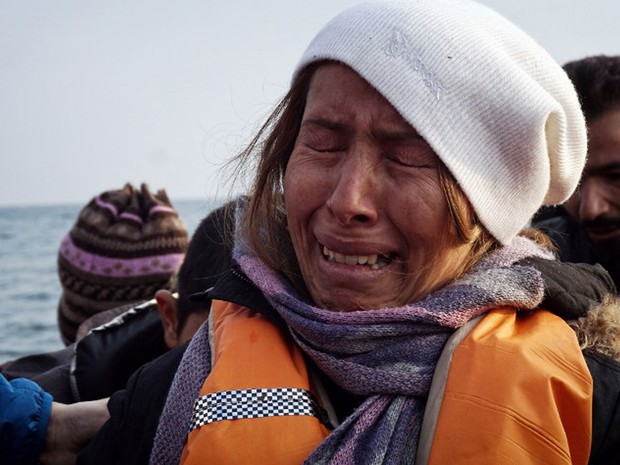 Mulher se emociona ao chegar em bote à Ilha de Lesbos, na costa grega, no domingo (20), quando novo acordo entre União Europeia e Turquia começou a valer (Foto: STR / AFP)