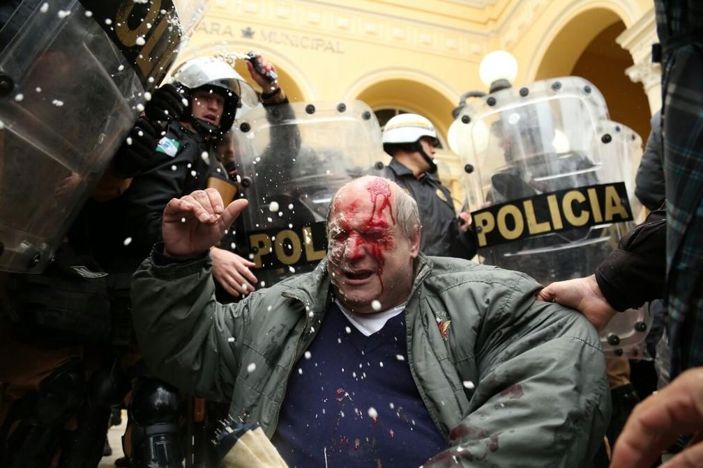 Manifestante ficou ferido em frente à Câmara Municipal de Curitiba (Foto: Rodrigo Fonseca)