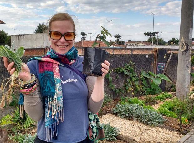 Moradora colhe alimentos plantados em espaço público (Foto: Reprodução/Facebook)