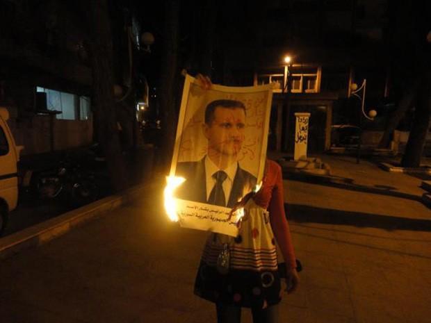 Manifestante antirregime  ondeima cartaz aofoto do presidente Bashar al Assad, em Damasco (Foto: AFP)