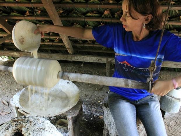 Guia de turismo demonstra processo de defumação do látex, onde muitos morriam de tuberculose  (Foto: Tiago Melo/G1 AM)