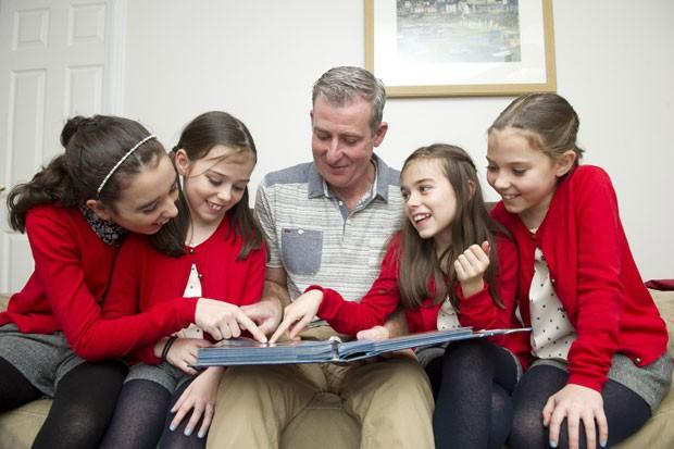 Mark Worthington e suas quatro filhas olham um álbum de fotos de família após a morte da mãe. A filha mais velha está terminando de descrever o guia que a mãe deixou para a educação delas (Foto: PIC BY DAN ROWLANDS / CATERS NEWS)
